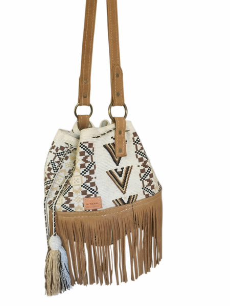 Side angle image of Wayuu bucket bag purse with brown leather strap and fringe and tassels; bag is white base with brown, dark brown and tan design