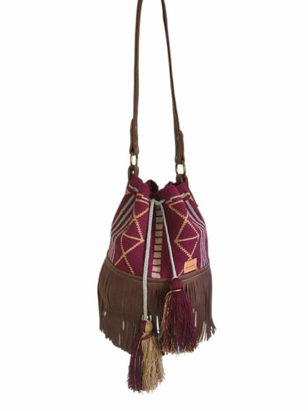 Image of Wayuu bucket bag purse with brown leather strap and fringe and tassels; bag is maroon with gray and tan detail