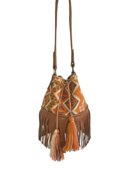 Image of Wayuu one strand bucket bag purse with brown leather strap and fringe and tassels; bag light tan with orange and gray geometrical design