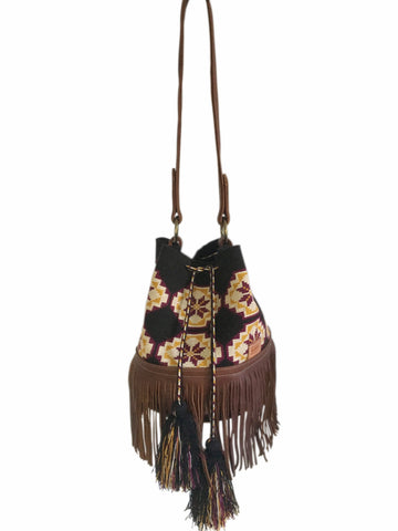 Image of one strand Wayuu bucket bag purse with brown leather strap and fringe and tassels; bag is black with tan, mustard yellow and burgundy flower design