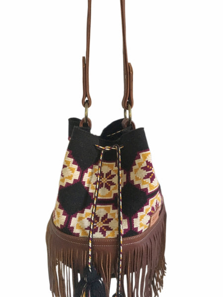 Close up image of one strand Wayuu bucket bag purse with brown leather strap and fringe and tassels; bag is black with tan, mustard yellow and burgundy flower design