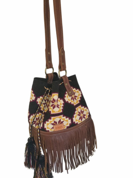 Side angle image of one strand Wayuu bucket bag purse with brown leather strap and fringe and tassels; bag is black with tan, mustard yellow and burgundy flower design