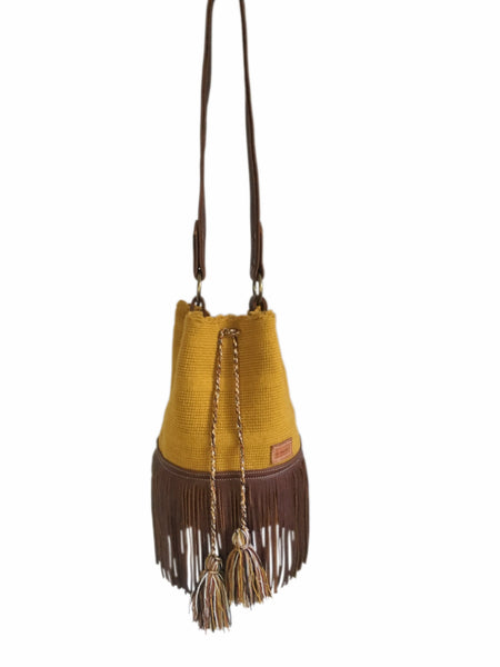 Image of Wayuu one strand bucket bag purse with brown leather strap and fringe and tassels; bag is solid color mustard yellow