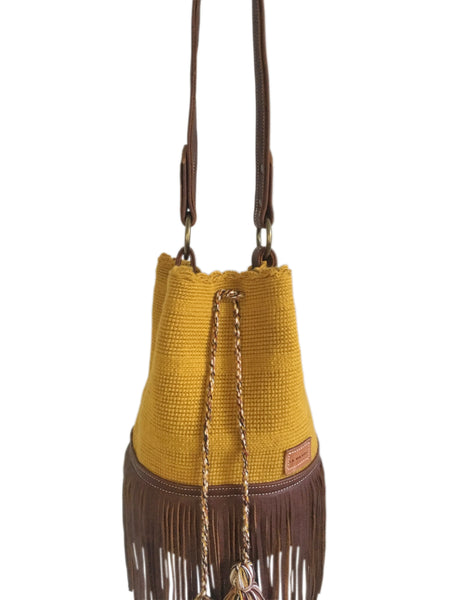 Close up image of Wayuu one strand bucket bag purse with brown leather strap and fringe and tassels; bag is solid color mustard yellow