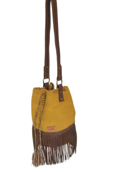 Side angle image of Wayuu one strand bucket bag purse with brown leather strap and fringe and tassels; bag is solid color mustard yellow