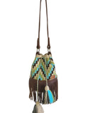 Image of one strand Wayuu bucket bag purse with brown leather strap and fringe and tassels; bag is light tan with dark brown, lime green, blue square step design