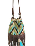 Close up image of one strand Wayuu bucket bag purse with brown leather strap and fringe and tassels; bag is light tan with dark brown, lime green, blue square step design