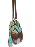 Side angle image of one strand Wayuu bucket bag purse with brown leather strap and fringe and tassels; bag is light tan with dark brown, lime green, blue square step design