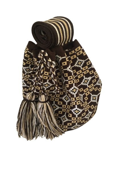 Side angle image of una hebra Wayuu mochila purse, drawstring crossbody bag with tassels - base color chocolate brown with tan, white and black design