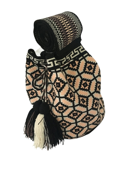Side angle image of una hebra Wayuu mochila purse, drawstring crossbody bag with tassels - base color black with pink peach, white and purple grey design