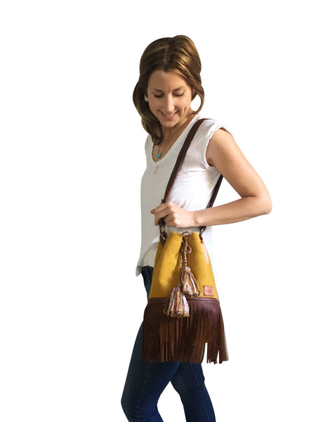On body image of Wayuu one strand bucket bag purse with brown leather strap and fringe and tassels; bag is solid color mustard yellow