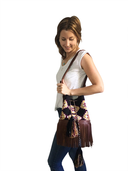 On body image of one strand Wayuu bucket bag purse with brown leather strap and fringe and tassels; bag is black with tan, mustard yellow and burgundy flower design