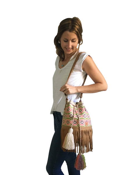 On body image of Wayuu bucket bag purse with caramel brown leather strap, fringe with drawstring and tassels; bag is tan with light brown, light pink and light green circular design