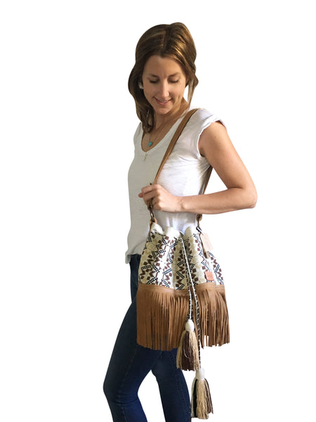On body image of Wayuu bucket bag purse with brown leather strap and fringe and tassels; bag is white base with brown, dark brown and tan design