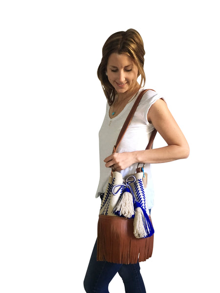 On body image of Wayuu bucket bag purse with brown leather strap and fringe and tassels; bag is light tan with blue design