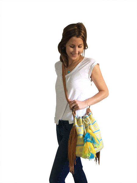 On body image of one strand Wayuu bucket bag purse with brown leather strap and fringe and tassels; bag is light tan with bright yellow and orange squares and blue lines