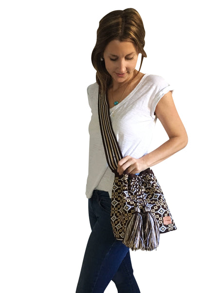 On body image of una hebra Wayuu mochila purse, drawstring crossbody bag with tassels - base color chocolate brown with tan, white and black design