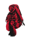 Side angle image of dos hebra Wayuu mochila purse, drawstring crossbody bag with tassels - bag is red base with black triangle design