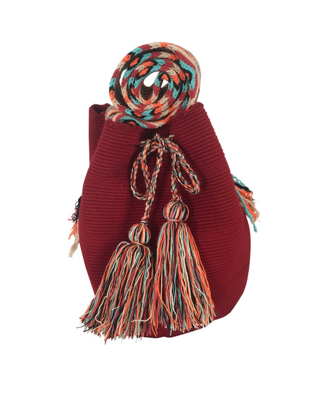 Image of dos hebra Wayuu mochila purse, drawstring crossbody bag with tassels and cloth strap; mochila is solid brick red with colorful strap