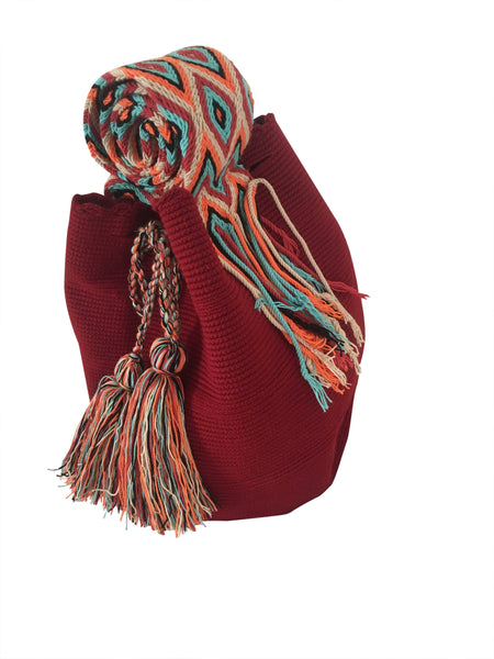 Side angle image of dos hebra Wayuu mochila purse, drawstring crossbody bag with tassels and cloth strap; mochila is solid brick red with colorful strap