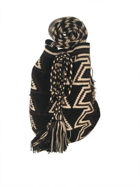 Image of dos hebra Wayuu mochila purse, drawstring crossbody bag with tassels - bag is black base with dark brown and tan geo design