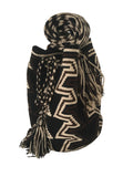 Side angle image of dos hebra Wayuu mochila purse, drawstring crossbody bag with tassels - bag is black base with dark brown and tan geo design