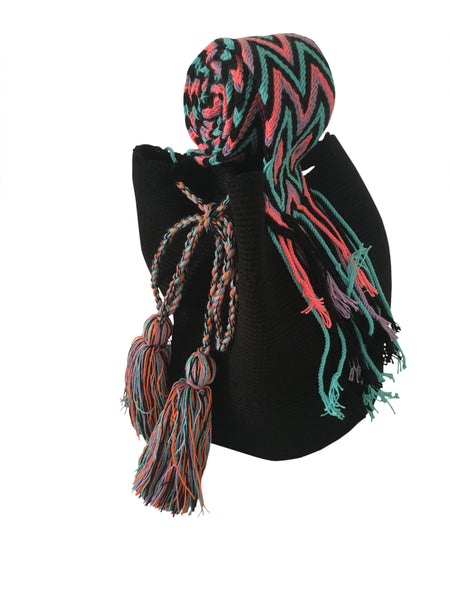 Side angle image of dos hebra Wayuu mochila purse, drawstring crossbody bag with tassels - bag is black with colorful strap and tassels
