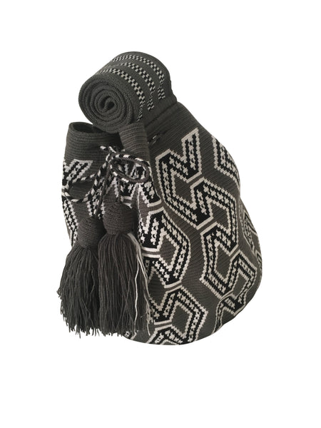 Side angle image of una hebra Wayuu mochila purse, drawstring crossbody bag with tassels - bag is grey base with white and black geometric design
