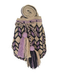 Image of una hebra Wayuu mochila purse, drawstring crossbody bag with tassels - bag is light tan base with purple and dark purple design