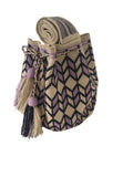 Side angle image of una hebra Wayuu mochila purse, drawstring crossbody bag with tassels - bag is light tan base with purple and dark purple design