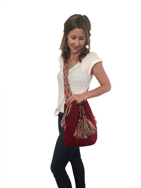 On body image of dos hebra Wayuu mochila purse, drawstring crossbody bag with tassels and cloth strap; mochila is solid brick red with colorful strap