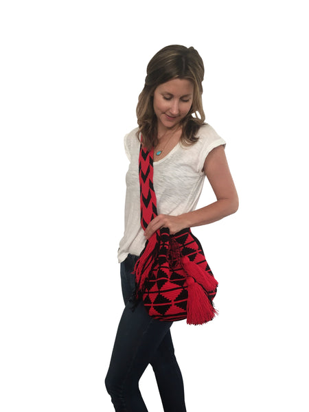 On body image of dos hebra Wayuu mochila purse, drawstring crossbody bag with tassels - bag is red base with black triangle design