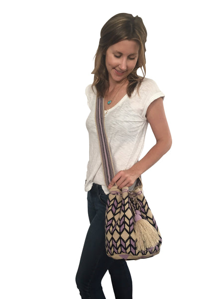On body image of una hebra Wayuu mochila purse, drawstring crossbody bag with tassels - bag is light tan base with purple and dark purple design