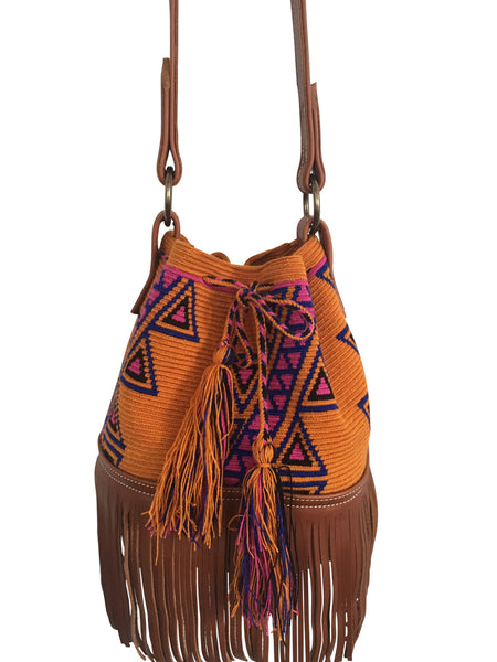 Close up image of Wayuu bucket bag purse with brown leather strap and fringe; bag is dirt orange base color with pink-purple and blue design