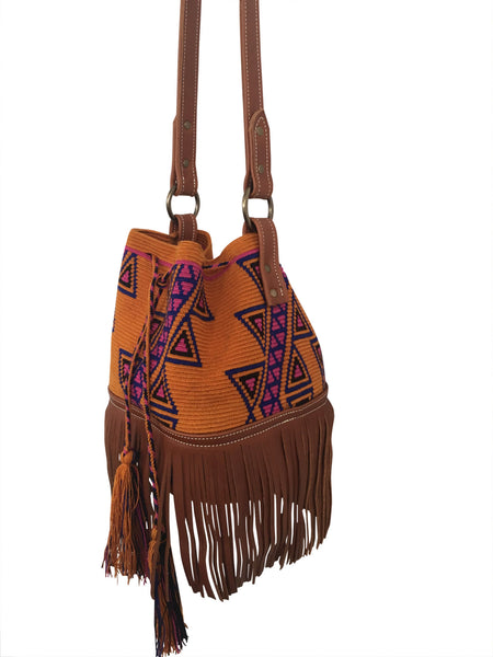 Side angle image of Wayuu bucket bag purse with brown leather strap and fringe; bag is dirt orange base color with pink-purple and blue design