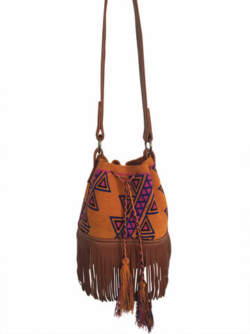 Image of Wayuu bucket bag purse with brown leather strap and fringe; bag is dirt orange base color with pink-purple and blue design