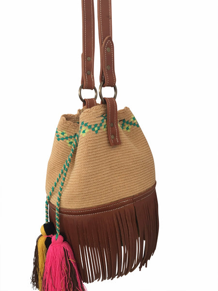 Side angle image of Wayuu bucket bag purse with brown leather strap and fringe; bag is tan with lime green + aqua detail at top