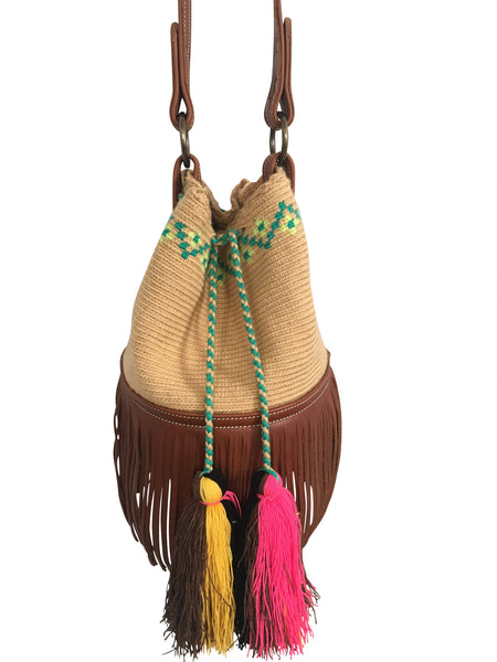 Close up image of Wayuu bucket bag purse with brown leather strap and fringe; bag is tan with lime green + aqua detail at top