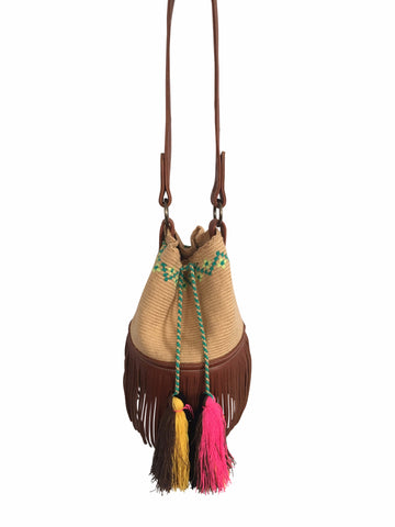 Image of Wayuu bucket bag purse with brown leather strap and fringe; bag is tan with lime green + aqua detail at top