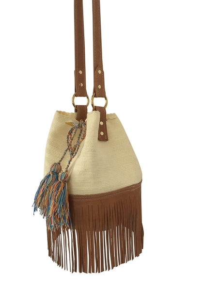 Side angle image of Wayuu bucket bag purse with brown leather strap and fringe; bag is cream white with shades of blue tassels