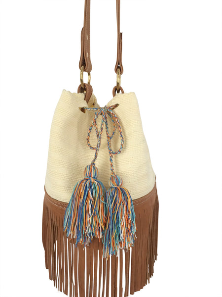 Close up image of Wayuu bucket bag purse with brown leather strap and fringe; bag is cream white with shades of blue tassels