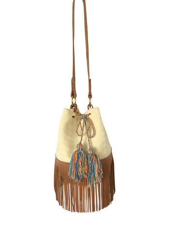 Image of Wayuu bucket bag purse with brown leather strap and fringe; bag is cream white with shades of blue tassels