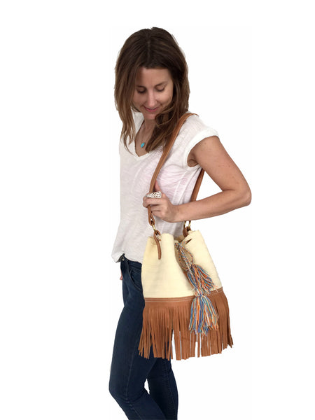 On body image of Wayuu bucket bag purse with brown leather strap and fringe; bag is cream white with shades of blue tassels