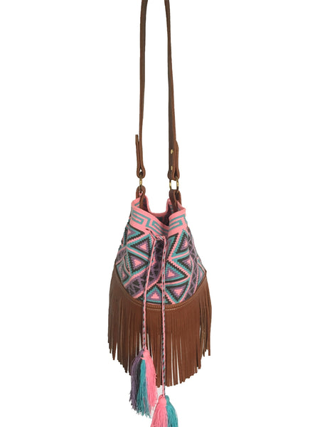 Image of Wayuu bucket bag purse with brown leather strap and fringe; bag is pink base with grey, purple and blue geometric design