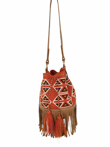 Image of Wayuu bucket bag purse with brown leather strap and fringe; bag is dirty orange base with brown, white and deep yellow geometrical design