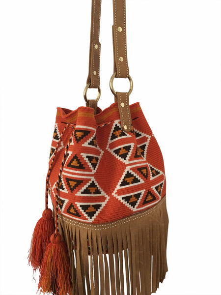 Side angle image of Wayuu bucket bag purse with brown leather strap and fringe; bag is dirty orange base with brown, white and deep yellow geometrical design