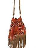 Close up image of Wayuu bucket bag purse with brown leather strap and fringe; bag is dirty orange base with brown, white and deep yellow geometrical design