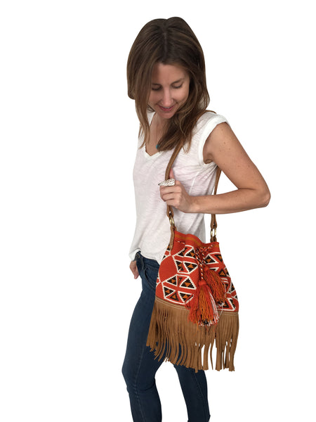 On body image of Wayuu bucket bag purse with brown leather strap and fringe; bag is dirty orange base with brown, white and deep yellow geometrical design