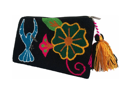 Close up image of Wayuu small clutch purse with tassel and zipper; rectangular shape with black base blue bird and flower detail