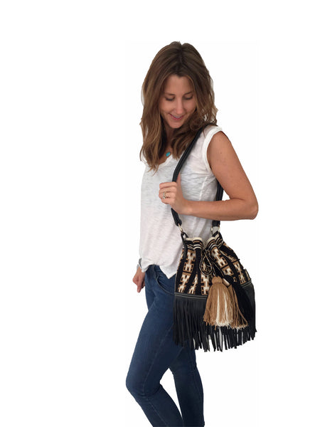 On body image of Wayuu mochila purse with black leather strap and fringe; bag is black with tan and white detail